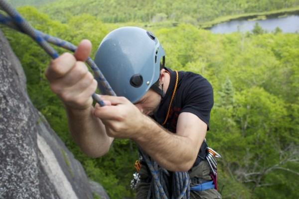 Jared Garfield, manager of Rental Equipment and Repairs at the Mainebound Adventure Center, switches positions at an anchor and belaying point on the 5.7+ route Highlander at Eagle Bluff in Clifton, Maine.