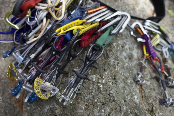 Jared Garfield, Manager of Rental Equipment and Repairs at the Mainebound Adventure Center, lays out his rack of cams and nuts before lead climbing at Eagle Bluff in Clifton, Maine.