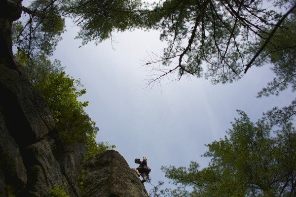Jared Garfield, Manager of Rental Equipment and Repairs at the Mainebound Adventure Center, climbs the 5.6 route Pride and Joy as a warm up at Eagle Bluff in Clifton, Maine.