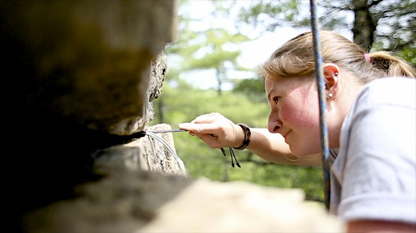 Hilary Butrock removes a nut while climbing Pride and joy, a 5.6 route at Eagle Bluff in Clifton, Maine.