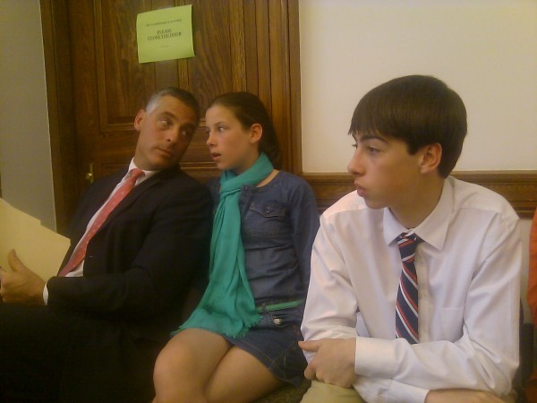 David J. Mitchell (left) of Calais consults Wednesday with his daughter, Emily Mitchell, 12, while the two wait with son, Greg Mitchell, 13, for the Judiciary Committee to vote on his nomination to be a District Court judge in Washington County. The committee unanimously recommended that Mitchell be confirmed by the Senate.