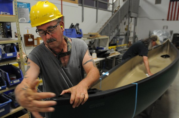 John Sibley puts trim on a canoe at the end of the assembly line at Johnson Outdoors in Old Town on Monday.