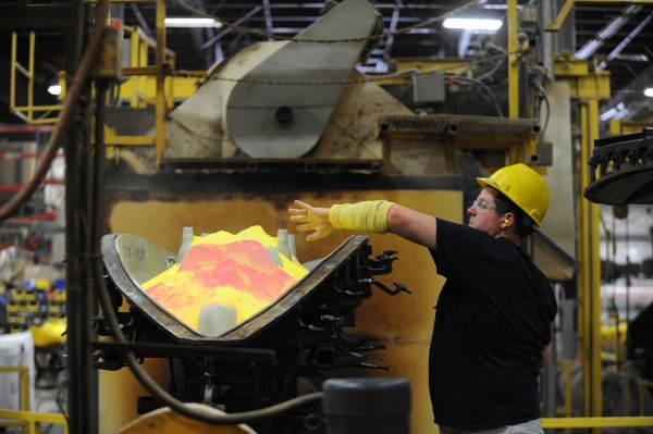Scott Brasslett puts finely ground polyethylene into a mold to make the company's new Predator watercraft at Johnson Outdoors in Old Town on Monday.