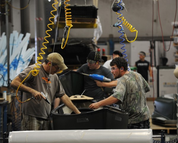 Assembly line workers at Johnson Outdoors in Old Town finish off canoes on Monday.