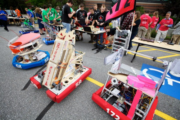 Students show off their their disc-flinging mobile units in the parking lot at Fairchild Semiconductor in South Portland Thursday as part of the launch of the Robotics Institute of Maine.