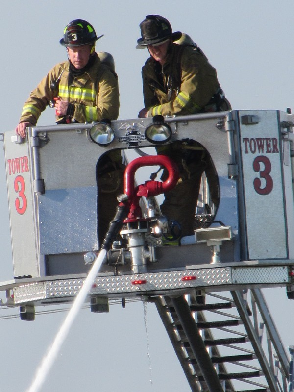 Rockland Firefighter Chris Whytock, left, and Lt. Jamie Leo man the bucket on top of the Rockland Fire Department's ladder truck to try to extinguish a fire at the city dump on Wednesday afternoon.