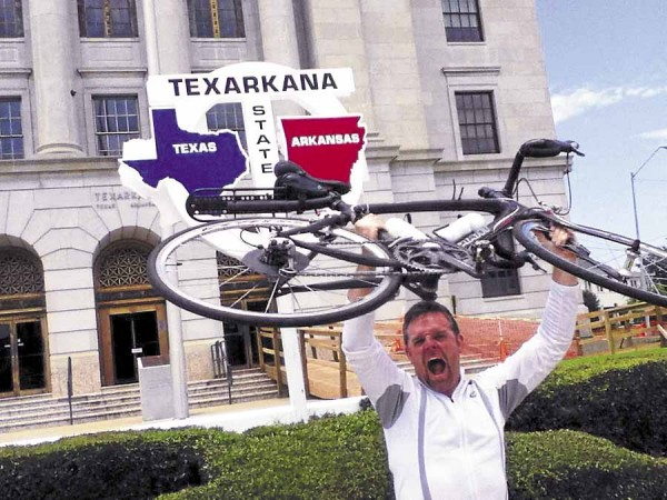 After pedaling many, many miles from Maine, Chris Quimby of Brooks triumphantly lifts his bike over his head after reaching the Texas state line in Texarkana. Quimby crossed his finish line at Rockwall, Texas on Friday, June 21.