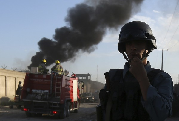 An Afghan policeman keeps watch as smoke rises from the site of an attack in Kabul, July 2, 2013.