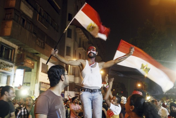 An anti-Morsi protester dances as people celebrate near Tahrir square after the announcement of the removal from office of Egypt's deposed President Mohamed Mursi in Cairo, July 3, 2013.
