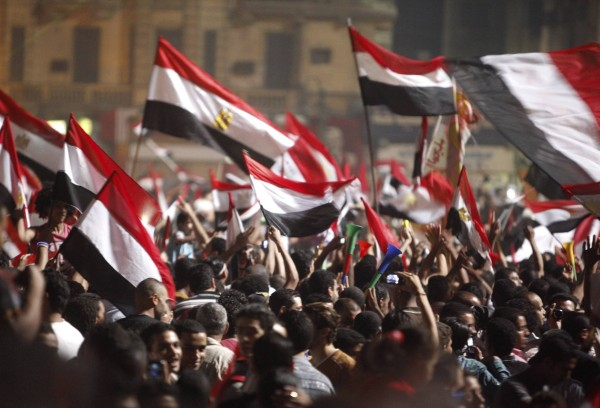 Anti-Morsi protesters walk with their flags as they celebrate in Tahrir square after the announcement of the removal from office of Egypt's deposed President Mohamed Mursi in Cairo, July 3, 2013.