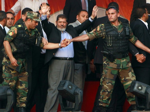 Egypt's Islamist President-elect Mohamed Morsi waves to his supporters while surrounded by members of the presidential guard in Cairo's Tahrir Square in this June 29, 2012 file photo.