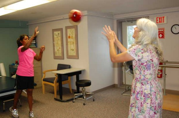 Army military policewoman Sgt. Helaina Lake, left, throws a weighted ball to occupational therapist Alice VanDerwerken on Tuesday at the Stanley Health Center in Farmington. Lake is making progress in her recovery from serious injuries suffered in a suicide-bombing on June 20, 2012, in Afghanistan.
