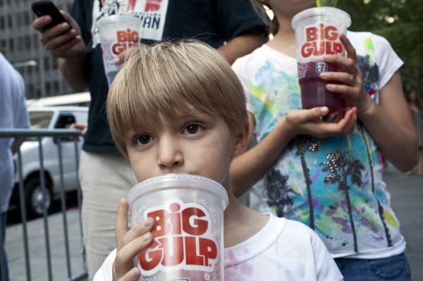 Benjamin Lesczynski, 8, of New York, takes a sip of a &quotBig Gulp&quot while protesting the proposed &quotsoda-ban,&quot outside City Hall in New York in this file photo taken July 9, 2012.  New York City's plan to ban large sugary drinks from restaurants and other eateries was an illegal overreach of executive power, a state appeals court ruled on Tuesday, upholding a lower court decision in March that struck down the law.