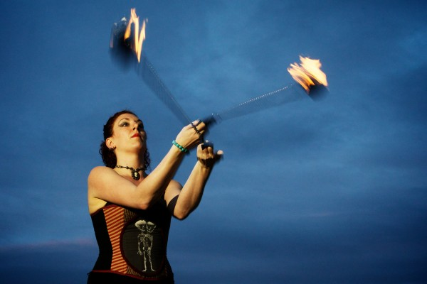Janice Pratt of Dark Follies swings fire poi on Portland's East End Beach Friday night. Dark Follies recently had a hand in writing new city rules regarding fire performing.