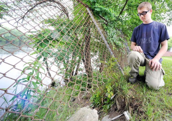 Andrew Bilodeau looks at the hole under a fence behind his house on River Street in Lewiston on Monday afternoon where last Friday he pulled an unconscious young boy from the Androscoggin River, background, and up under the fence to his father who performed CPR and other lifesaving techniques that saved the boy's life.