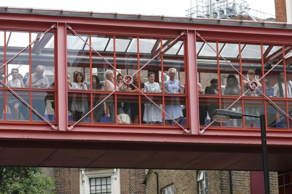 Hospital staff and visitors crowd an overhead walkway while awaiting the expected appearance of Britain's Catherine, Duchess of Cambridge, her baby boy and Prince William in London July 23, 2013. Prince William's wife Kate gave birth on Monday to a boy, who becomes third in line to the British throne, ending weeks of feverish speculation about the royal baby. The couple's first child was born at 4:24 p.m. (1524 GMT), weighing 8 lbs and 6 oz. His name will be announced at a later date but bookmakers favour George and James.