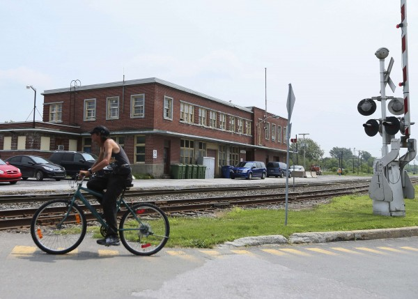 A cyclist rides past the building of the Maine, Montreal and Atlantic Railways (MMA), whose oil-tanker exploded last Saturday, in the town of Farnham, Quebec July 10, 2013. Sixty people are either dead or missing after the runaway train smashed into the center of the historic lakeside town of Lac Megantic and exploded early on Saturday morning.  Police say 200 investigators are sifting through the charred wreckage of what they describe as a crime scene. Only 15 bodies have been recovered, none of whom have yet been identified, and relatives hold out little hope that anyone will now be found alive.
