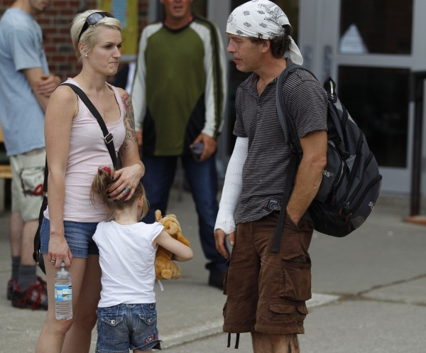 Survivor Bernard Thiberge (R) talks with other residents outside the school where the Red Cross has set up temporary shelter for evacuees in Lac Megantic, Quebec, July 10, 2013. Sixty people are either dead or missing after the runaway train smashed into the center of the historic lakeside town and exploded early on Saturday morning. Police say 200 investigators are sifting through the charred wreckage of what they describe as a crime scene. Only 15 bodies have been recovered, none of whom have yet been identified, and relatives hold out little hope that anyone will now be found alive.