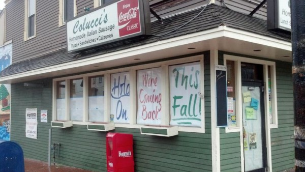Window posters foretell the reopening of Colucci's Hilltop Market on Munjoy Hill in Portland.