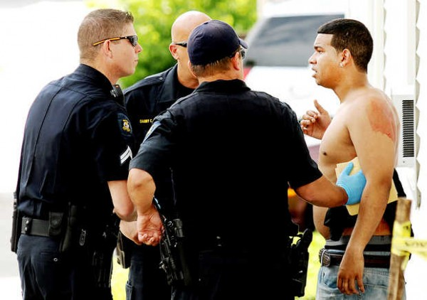 Lewiston Police officers talk with the stabbing victim at the corner of Birch and Knox streets in Lewiston on Thursday.