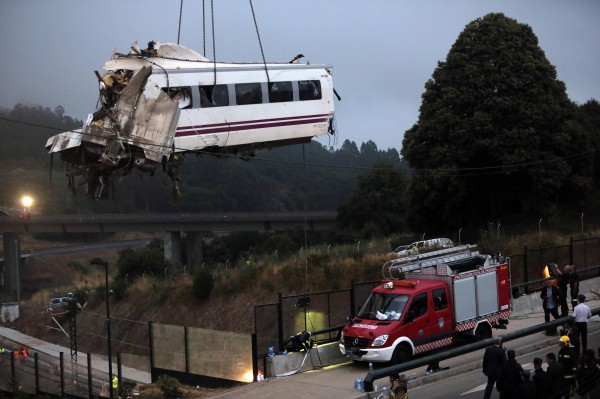 A crane removes a carriage from the tracks at the site of a train crash near Santiago de Compostela, northwestern Spain, July 25, 2013. A train derailed outside the ancient northwestern Spanish city of Santiago de Compostela on Wednesday evening, killing at least 77 people and injuring up to 131 in one of Europe's worst rail disasters.