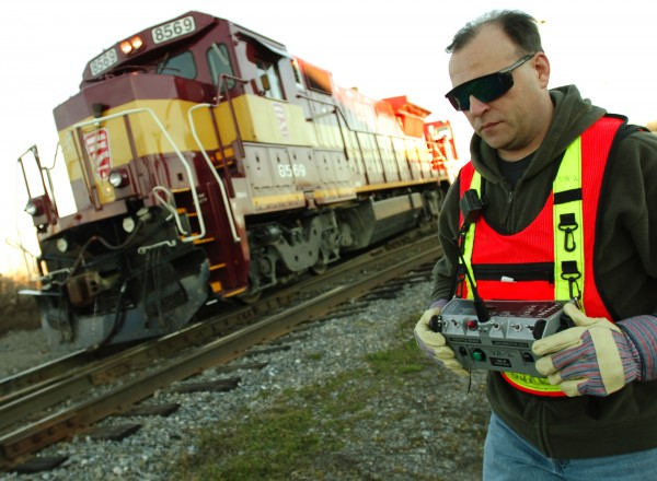 Montreal, Maine &  Atlantic Railway engineer Chuck Gould uses a remote control transmitter to move a locomotive at the railway's switching yard in Hermon.