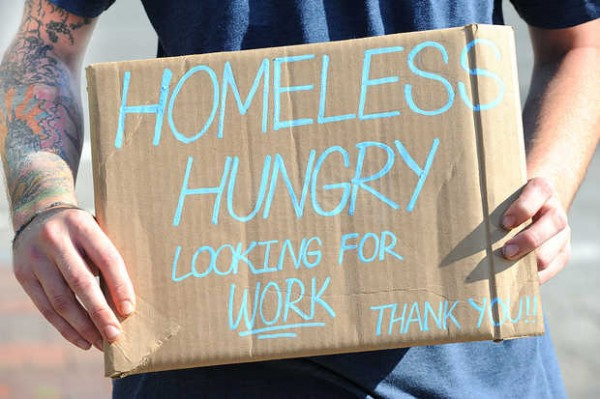 A panhandler on State Street holds a handmade sign in Portland recently.