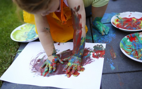 Two year-old Kaethe plays with paints in the garden of her home in Hanau, 18 miles south of Frankfurt, July 21, 2013. From August 1, 2013, all children in Germany between the age of 1 and 3 will have a legal entitlement to a place at a kindergarten.