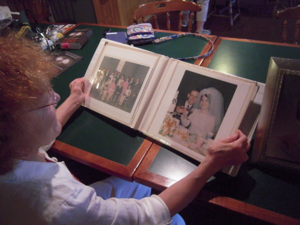 Philomena Baker looks at wedding photos of Angel Caron in an album a friend brought on June 26 to the Swamp Buck Restaurant in Fort Kent, where Philomena signed copies of her new book, &quotFlight to Freedom.&quot