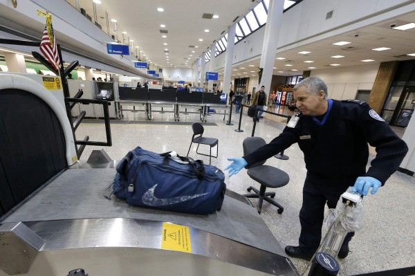A TSA security officer puts a bag through a scanner at the Salt Lake City international airport, in Salt Lake City, Utah.