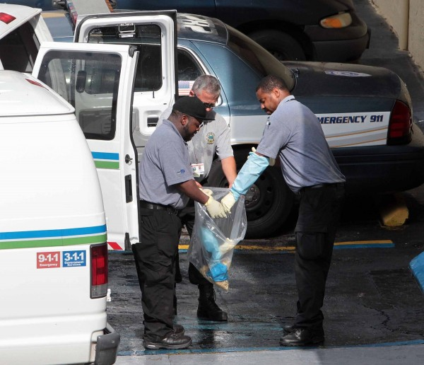 Members of the Department of the morgue of Miami-Dade County handle a plastic bag that was apparently used in the crime scene in the apartment complex located in Hialeah, Florida, where seven people died after a shooting.