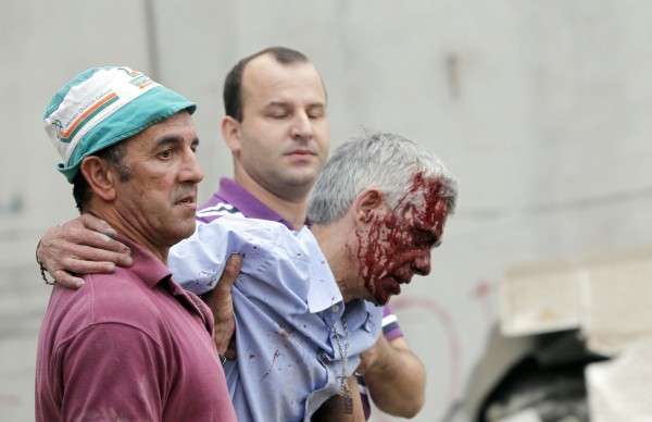 Train driver Francisco Jose Garzon, center, is helped by two men after his train crashed near Santiago de Compostela, northwestern Spain, July 24, 2013. Garzon, the driver of the Spanish train that derailed, killing at least 80 people, was under police guard in hospital on Thursday after the dramatic accident which an official source said was caused by excessive speed.