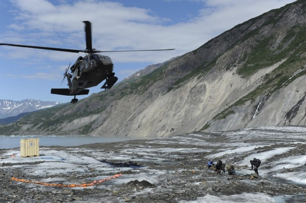 Members of a specialized investigative team from the Joint POW/MIA Accounting Command wait as a UH-60 Blackhawk helicopter comes in for a landing to transport them back to base after a day of assessing a historic aircraft crash site at Colony Glacier, Alaska, in this June 24, 2013 handout photo released to Reuters on July 8, 2013. An Alaska glacier is exposing remains from a military air tragedy six decades later. Relics from an Air Force cargo plane that slammed into a mountain in November 1952, killing all 52 servicemen on board, first emerged last summer on Colony Glacier, about 50 miles east of Anchorage.