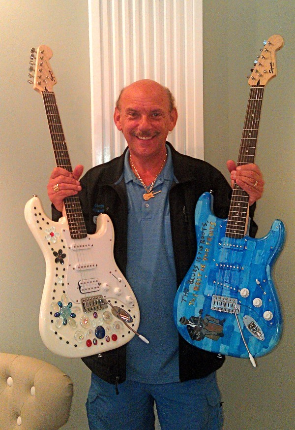 Paul Benjamin, founder of North Atlantic Blues Festival holds two Fender Guitars decorated by local artists to promote the 20th anniversary of the festival in Rockland next weekend.