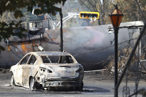 A burnt-out vehicle sits near the wreckage of a train car after a train derailment in Lac-Megantic, Quebec, on Sunday. A driverless freight train carrying tankers of petroleum products derailed at high speed and exploded into a giant fireball in the middle of the small Canadian town of Lac-Megantic early on Saturday, destroying dozens of buildings and leaving an unknown number of people feared missing.