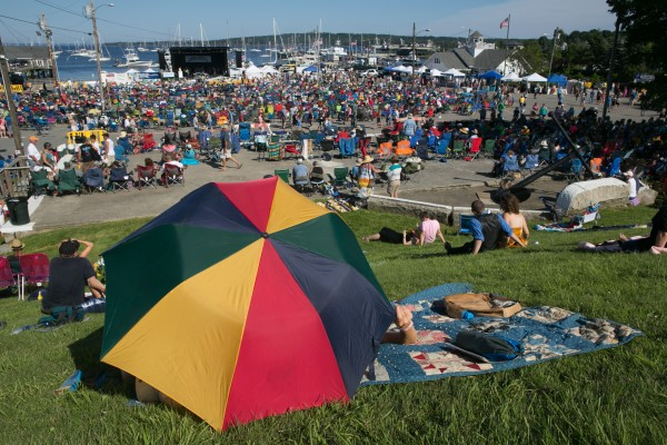 Fans guard themselves from the heat with an umbrella during the North Atlantic Blues Festival in Rockland on Saturday, July 13, 2013. This weekend marked the 20th anniversary of the festival.