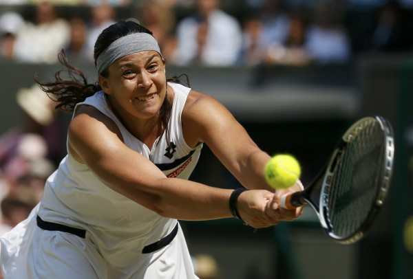 Marion Bartoli of France hits a return to Sabine Lisicki of Germany during their women's singles final tennis match at the Wimbledon Tennis Championships in London on Saturday. Bartoli defeated Lisicki 6-1, 6-4 for her first major title.