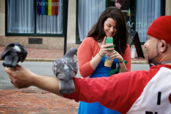 A woman photographs Starr Sarabia and his pigeon friends in Portland's Congress Square where Sarabia visits the flock nearly every day.