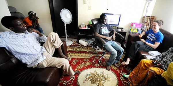 Erin Reed of Trinity Jubilee Center (right) talks with brothers Michaella Ousmane, 22 (left), Amandou Ousmane, 13 (center) and Younoussa Ousmane, 18, in Michaella's one-bedroom Lewiston apartment they share with their mother and another brother, both in wheelchairs due to polio.