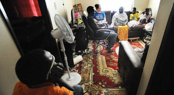 Amandou Ousmane, 13 (left), sits in his mother's electric wheelchair in the hallway of a tiny one-bedroom apartment, listening to his mother, Maimouna Djouma (third from right), be interviewed by a reporter recently.
