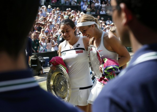 Marion Bartoli (left) of France walks off Center Court with Sabine Lisicki of Germany, after the trophy presentation, after Bartoli defeated Lisicki 6-1, 6-4 in the women's singles final at the Wimbledon Tennis Championships in London.