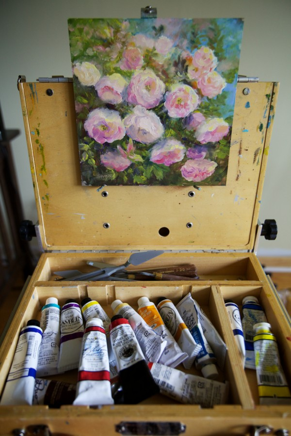 The neighbors' roses grace an oil punting in Suzanne Savage Brewer's living room in Sidney.