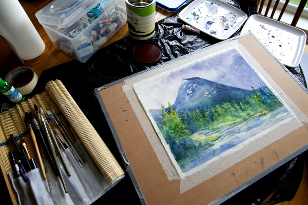 Suzanne Savage Brewer finishes up a watercolor painting at her kitchen table in Sidney.