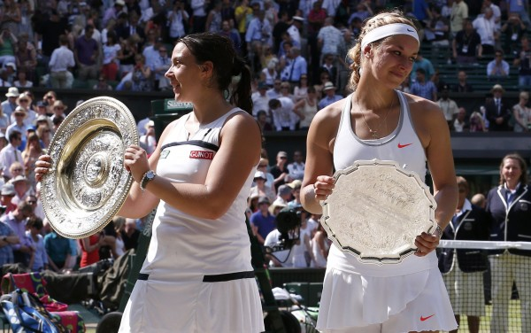 Marion Bartoli (left) of France holds her trophy, the Venus Rosewater Dish, after defeating Sabine Lisicki of Germany in women's singles final Saturday at the Wimbledon Tennis Championships in London.