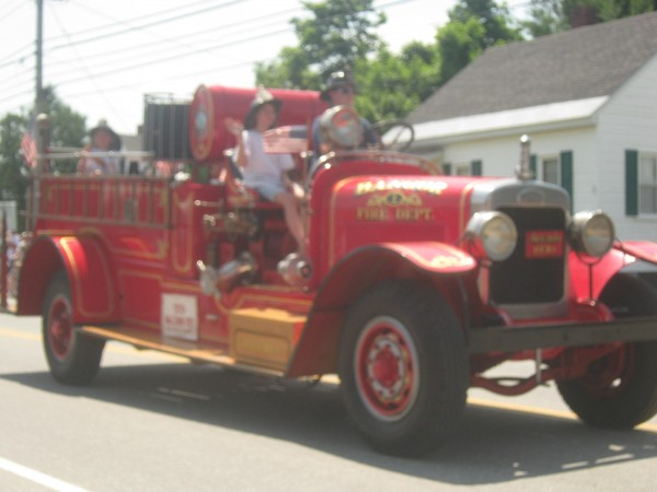 The antique tractor and antique firetruck ride-along in the Fourth of July parade in Bangor.