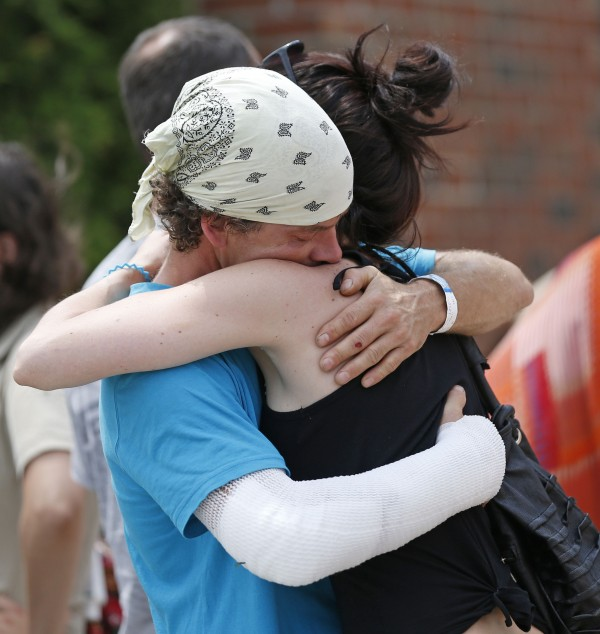 Bernard Trepanier (left), who said his arm was injured in the explosion, hugs his friend at the Polyvalente Montignac, the school sheltering the people who were forced to leave their houses after the explosion, in Lac-Megantic, on Sunday.