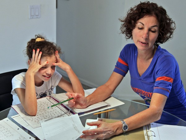 Haley Regent, left, shows her frustration while doing her math homework with her mother, Debbie Regent in 2012. Weston, Fla., resident Debbie Regent, 48, a working parent with two girls, supervises her children's homework.