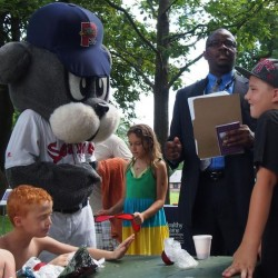 "Portland Superintendent of Schools Emmanuel Caulk reads the ""summer pledge"" to kids at a July 24 Deering Oaks Park event promoting the city's summer meals program as Slugger, the Portland Sea Dogs mascot, lends a paw. The pledge encourages kids to eat right, exercise and learn throughout the summer."