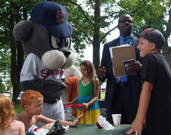 Portland Superintendent of Schools Emmanuel Caulk reads the &quotsummer pledge&quot to kids at a July 24 Deering Oaks Park event promoting the city's summer meals program as Slugger, the Portland Sea Dogs mascot, lends a paw. The pledge encourages kids to eat right, exercise and learn throughout the summer.