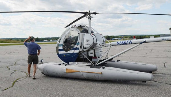 Ed Friedman inspects his helicopter before a flight over the Androscoggin River in August 2011.